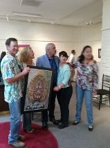 Garino's clients David and Bobbie Lundstrom accept a thank you poster of their commissioned art, the Virgen